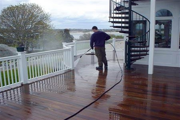 Man pressure washing a wood deck.